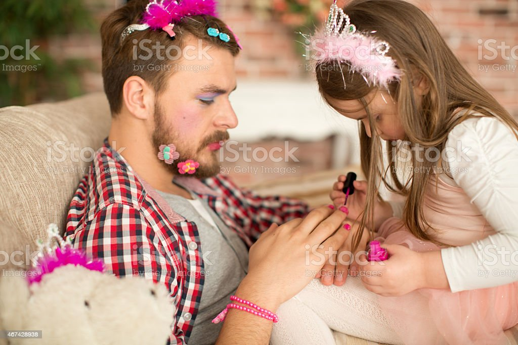 Cute daughter making up her father. stock photo