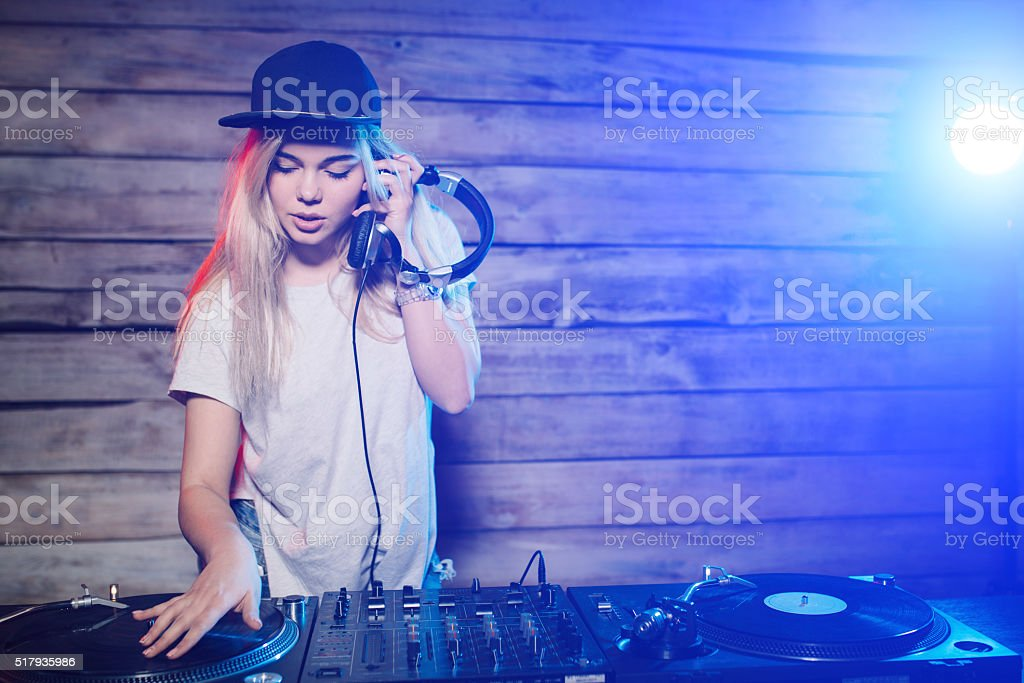 Cute dj woman having fun playing music at club party stock photo