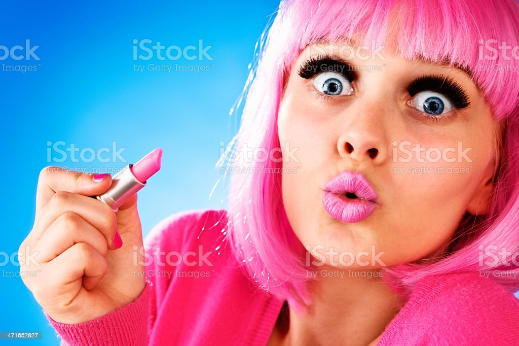 Cute, doll-like blonde teenager in pink wig applies lipstick stock photo