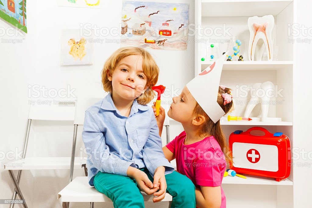 Cute ear nose throat specialist examining boy stock photo