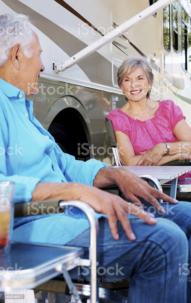 Cute elderly couple sitting by a caravan royalty-free stock photo