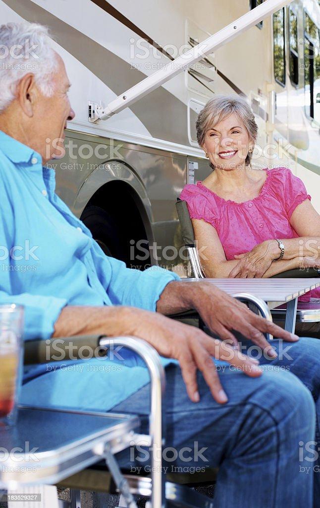 Cute elderly couple sitting by a caravan royalty-free stock photo