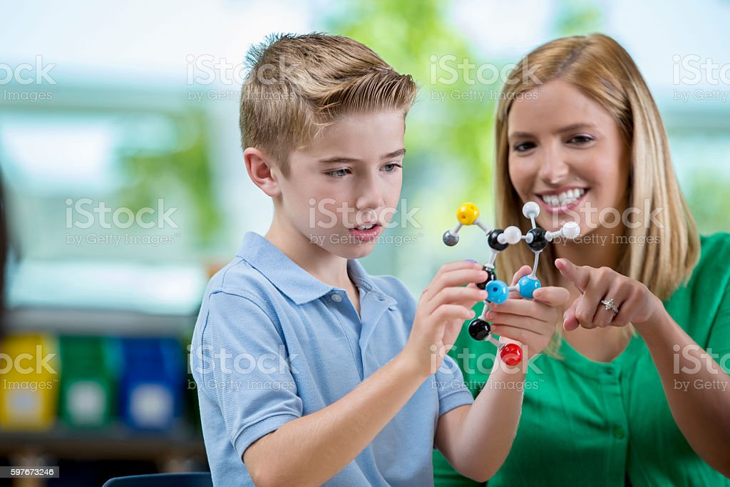 Cute elementary age student using molecule model with teacher stock photo