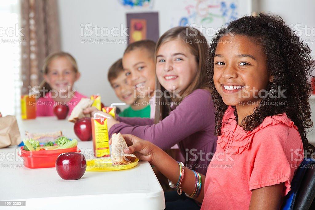 Cute elementary children having lunch at school stock photo