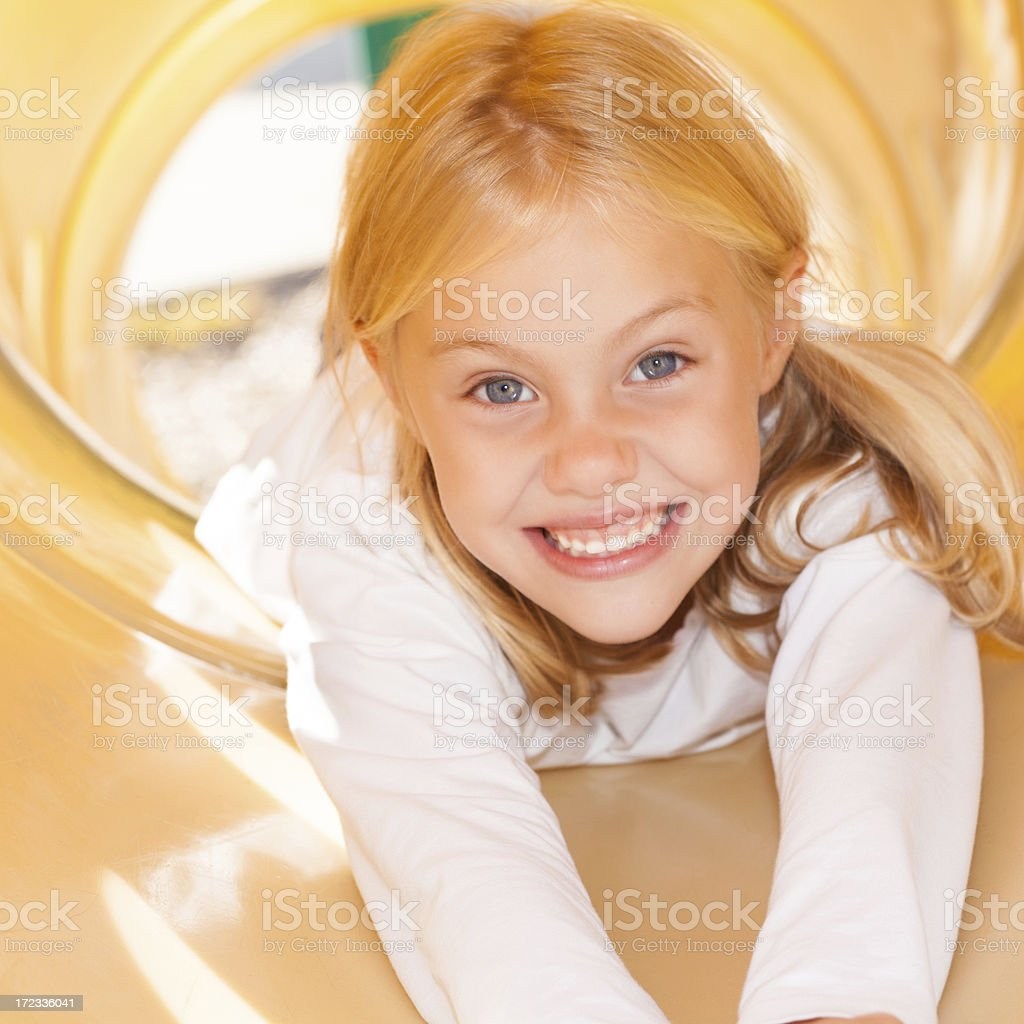 Cute elementary school girl on slide at recess royalty-free stock photo