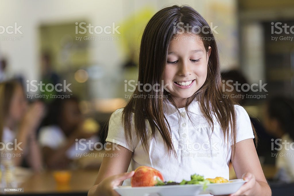Cute elementary student looking at tray of cafeteria food stock photo