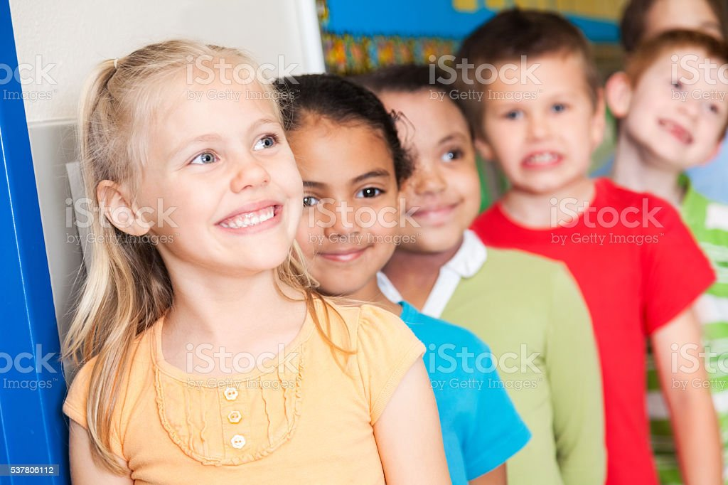 Cute elementary students line up quietly in hallway stock photo