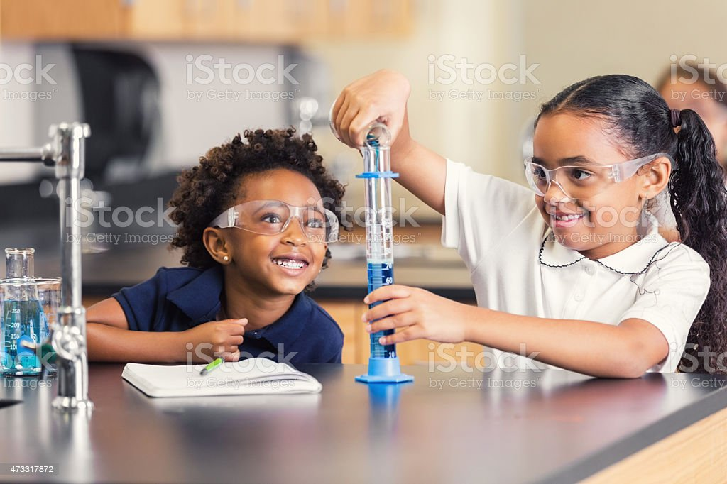 Cute elementary students smiling while doing science experiment in class stock photo