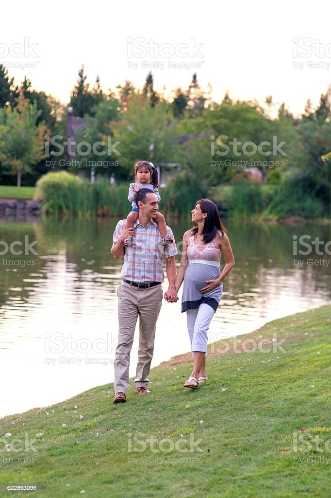 Cute ethnic family walking next to a pond stock photo