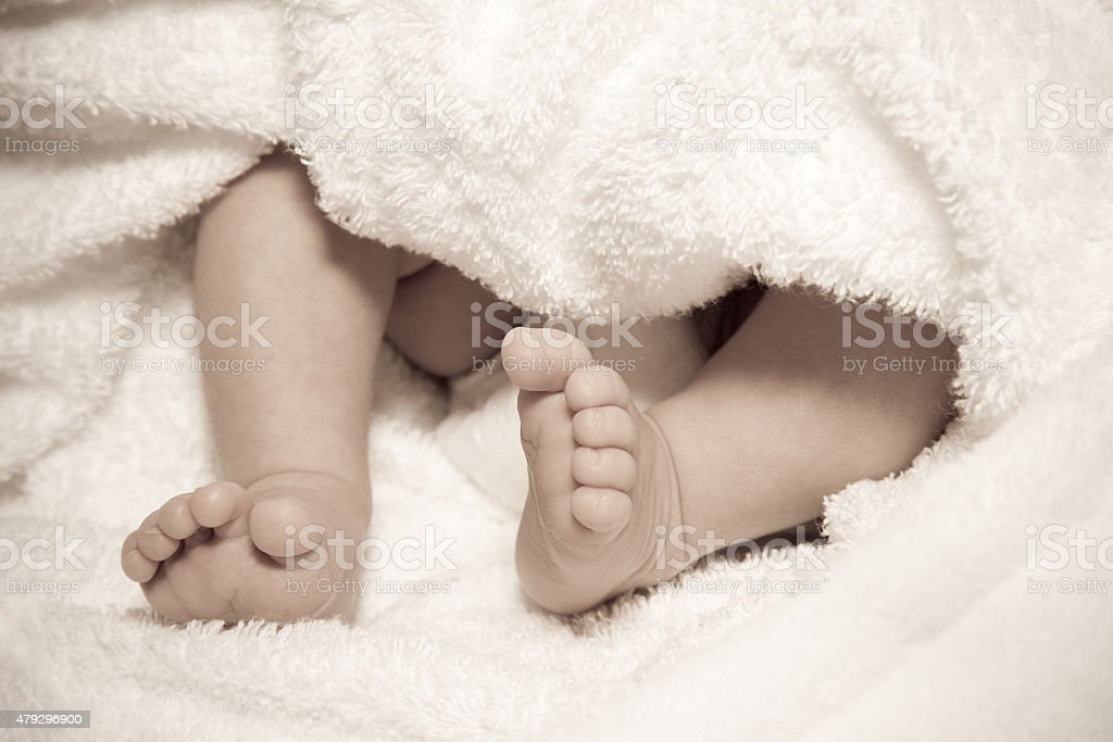 Cute feet of a two week old baby; sepia stock photo