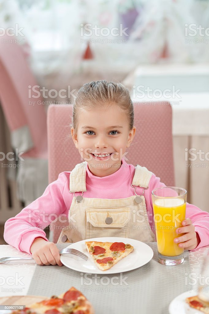 Cute female child has a dinner in cafe stock photo