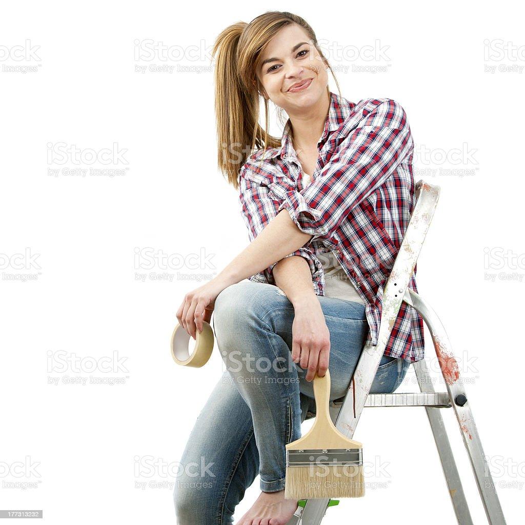 Jolie femme peintre assis sur échelle. photo libre de droits