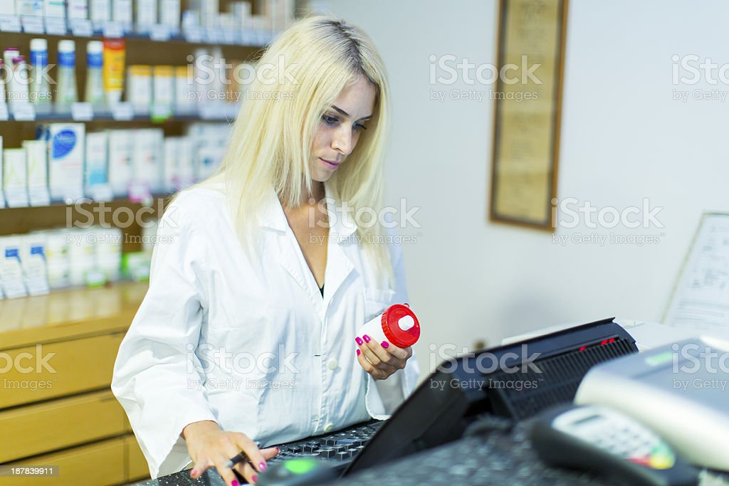 Cute female pharmacist at pharmacy checking supplies on a computer royalty-free stock photo