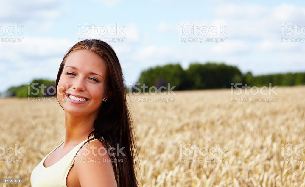Cute female smiling while at a field stock photo