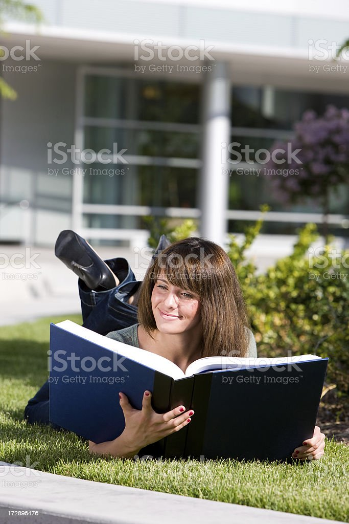 Cute Female Student Reading Oversized Book royalty-free stock photo