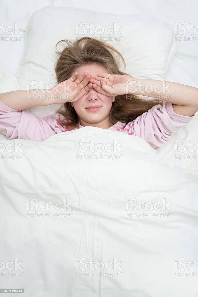 Cute Female Waking up in Bed and Rubing Her Eyes stock photo