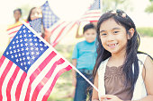 Cute Filipino girl holds American flag outdoors