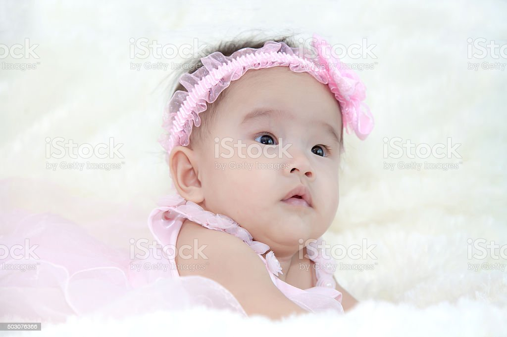 Cute five months asian baby in pink dress stock photo