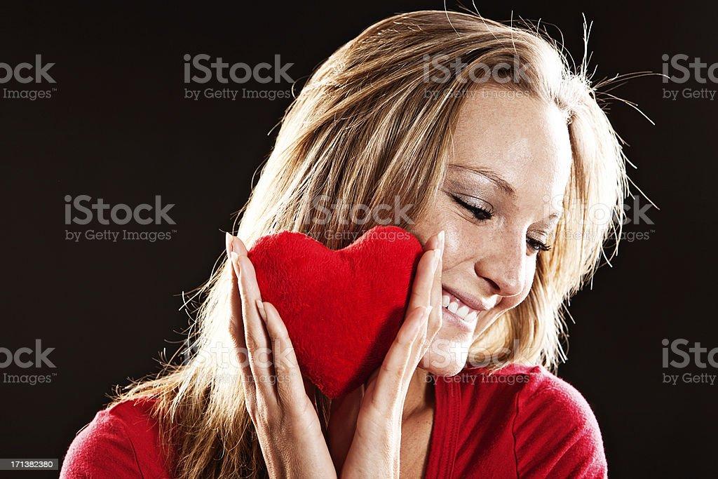 Cute, flirtatious, smiling blonde with red velvet heart stock photo