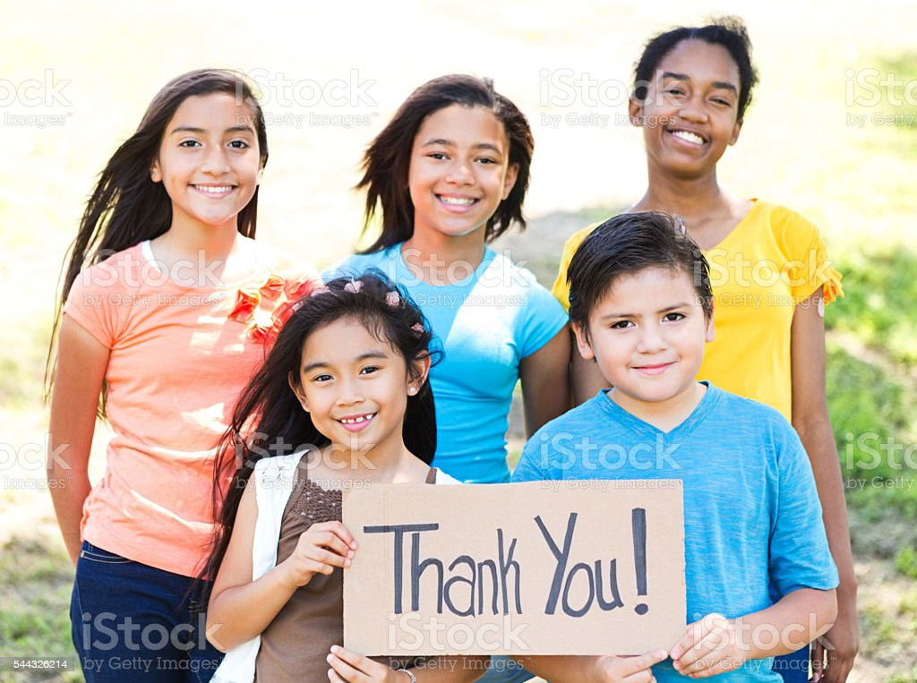 Cute friends hold 'Thank You!' sign in park stock photo
