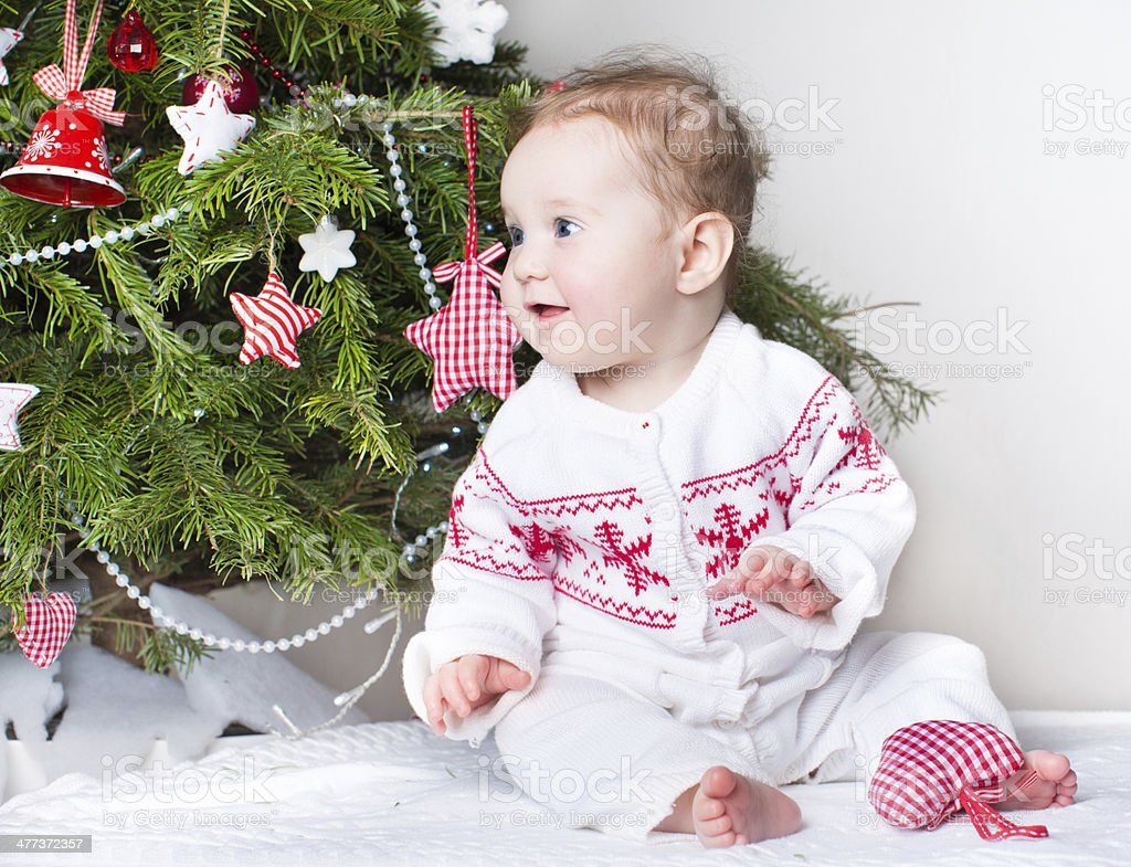 Cute funny baby girl playing under a Christmas tree royalty-free stock photo