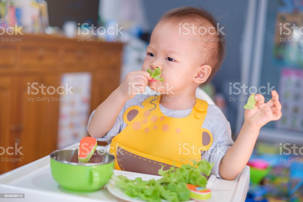 Cute funny little Asian 20 months toddler baby boy child sitting in high chair eating salad stock photo