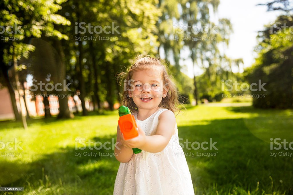 cute girl about to shoot water at camera royalty-free stock photo