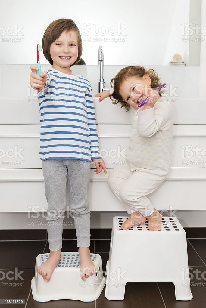 Cute girl and boy brushing teeth stock photo