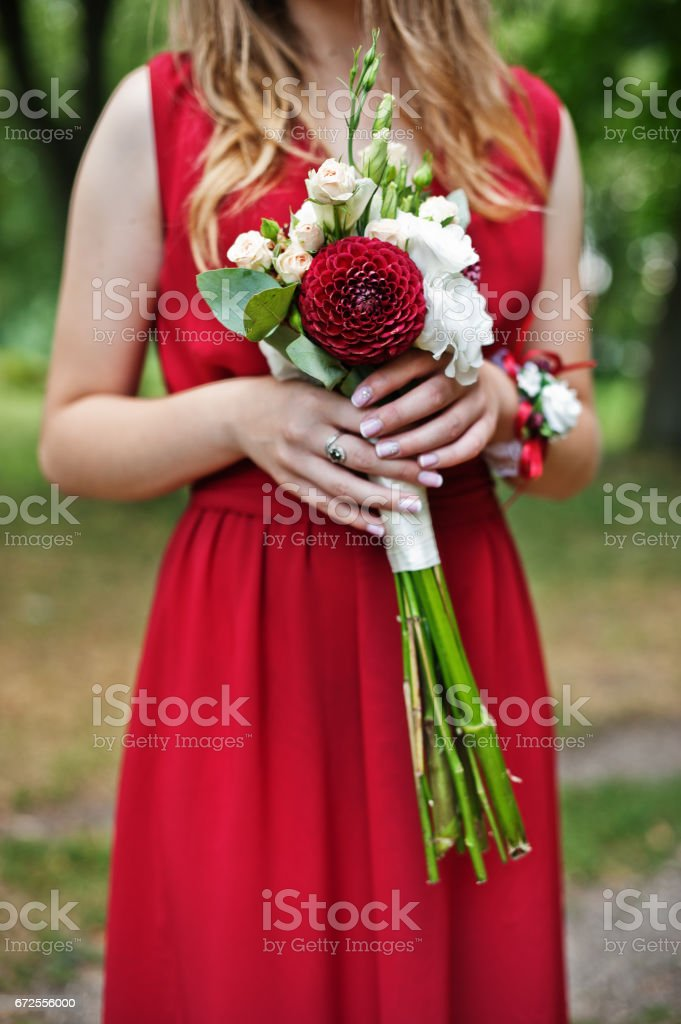 Cute girl bridesmaid at red dress with wedding bouquet at hand. stock photo