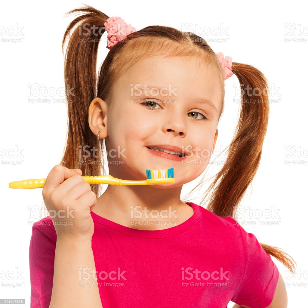 Cute girl brushing teeth with yellow toothbrush stock photo