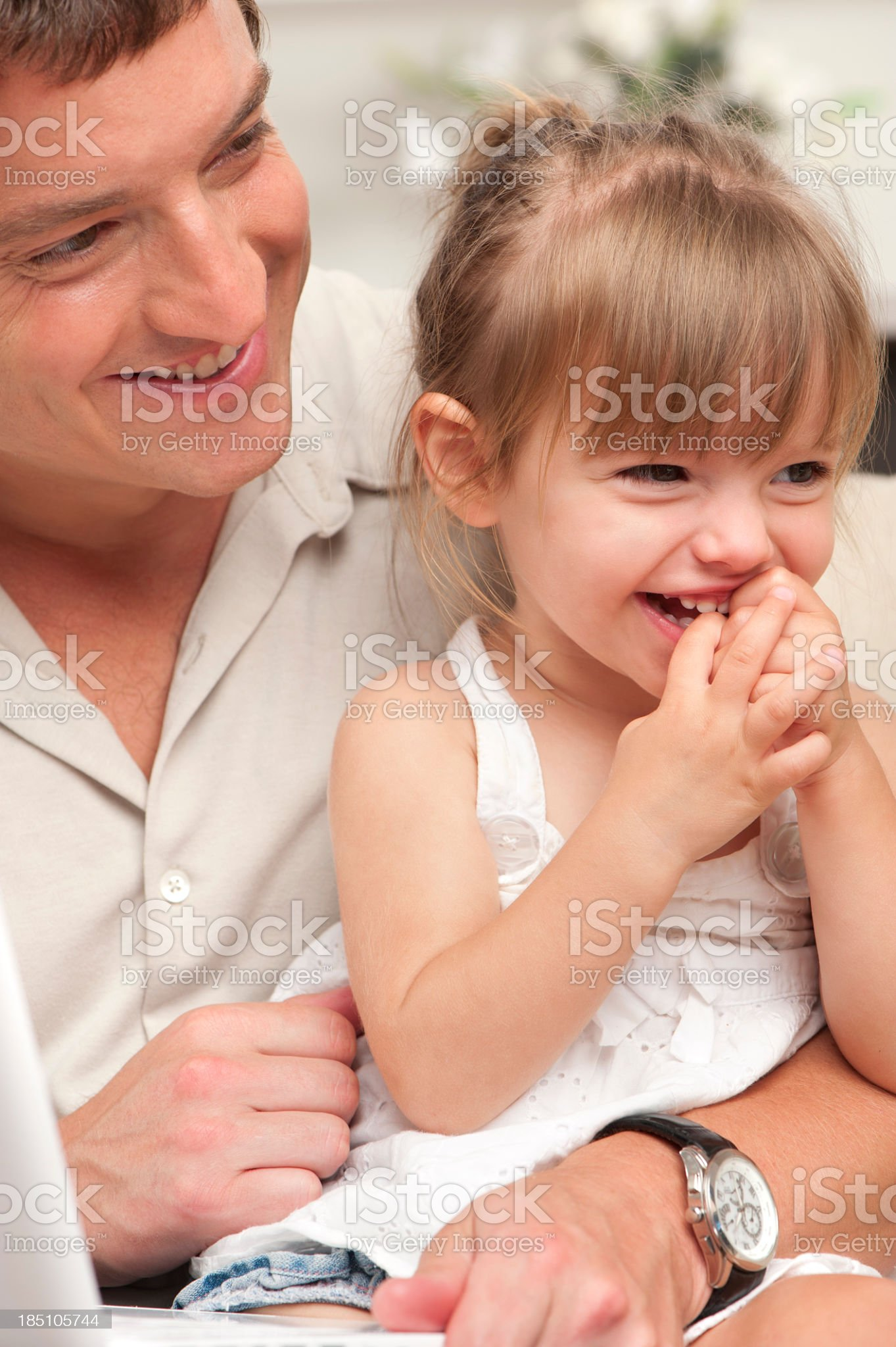 cute girl chewing fingers and laughing with father royalty-free stock photo