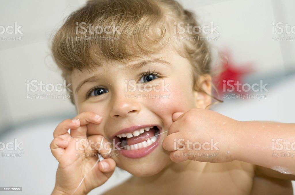 Cute girl cleaning teeth by floss in bathroom stock photo