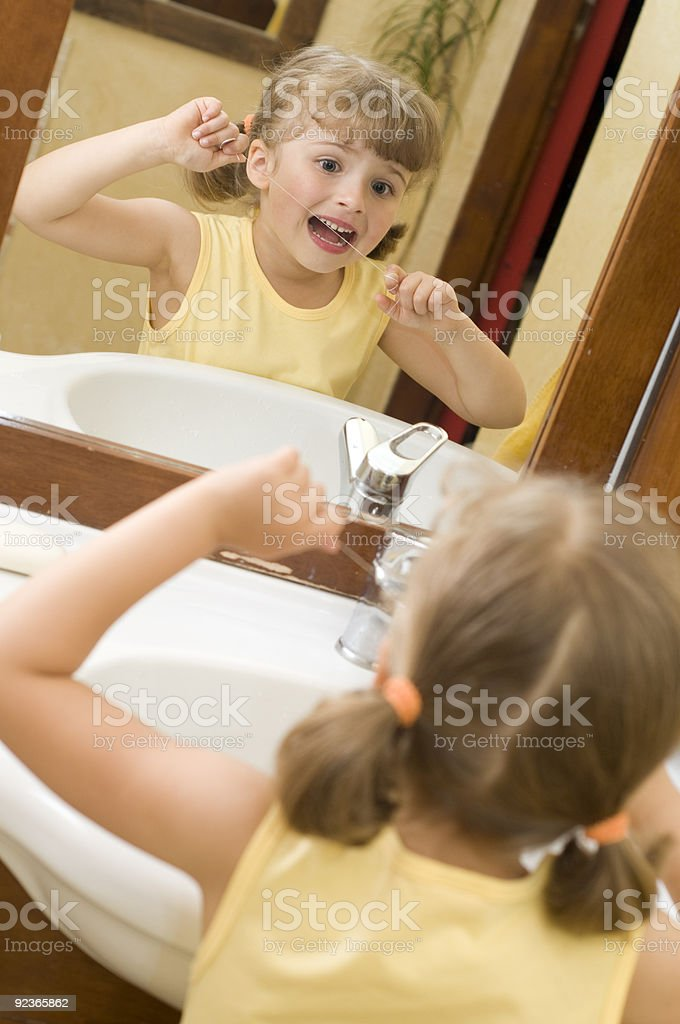 Cute girl cleaning teeth by floss royalty-free stock photo