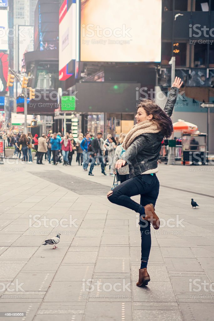 Cute girl dancing by herself in Time Square, New York. stock photo