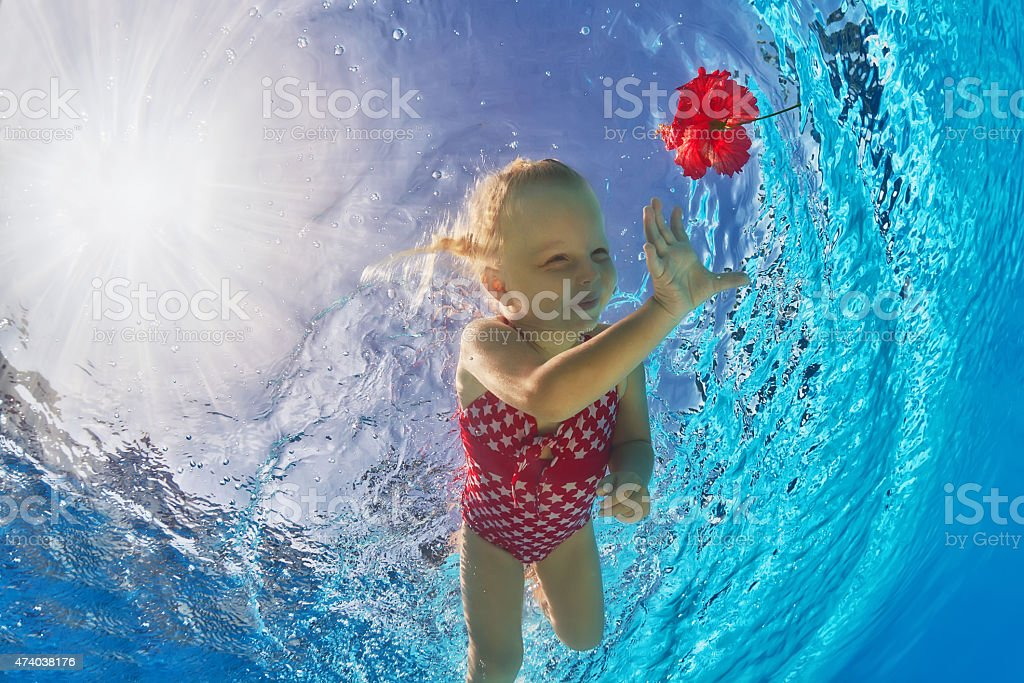 Cute girl diving underwater in the pool for red flower stock photo