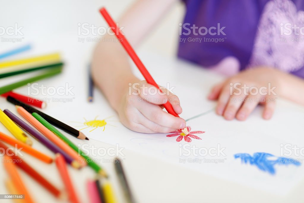 Cute girl drawing a picture with colorful pencils stock photo