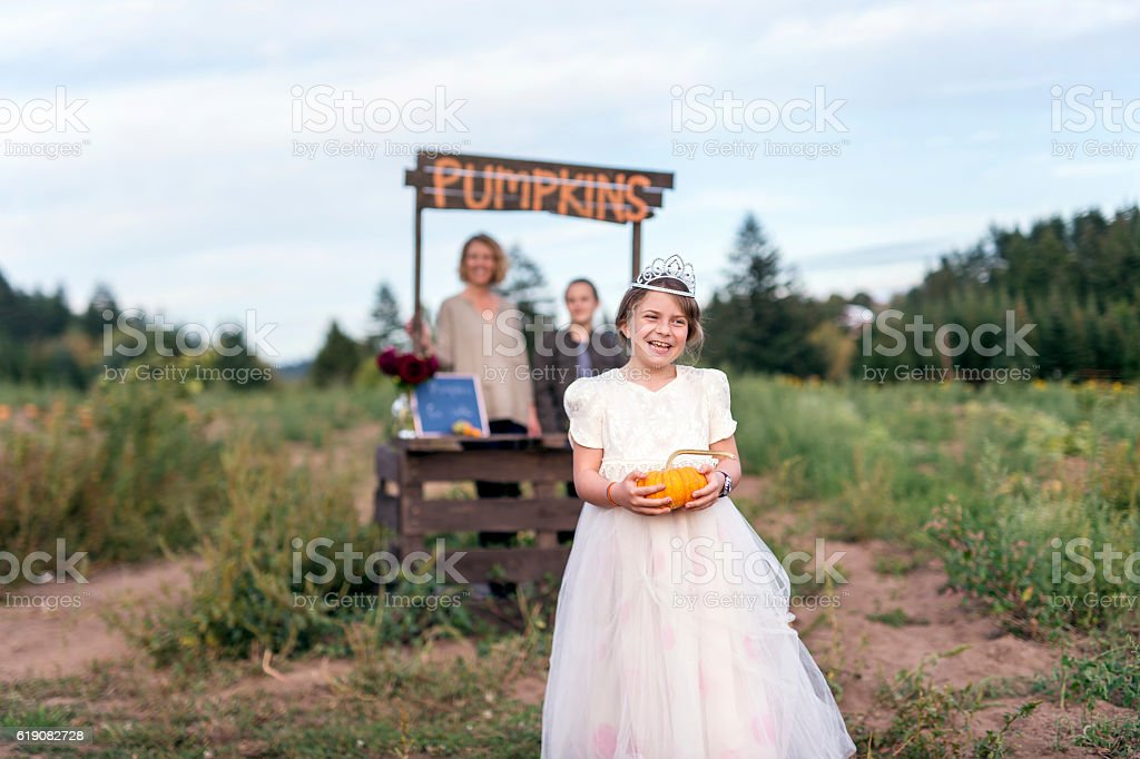 Cute girl dressed as a princess for halloween holding pumpkins stock photo
