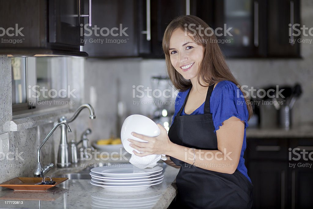 Cute girl drying dishes in the kitchen royalty-free stock photo