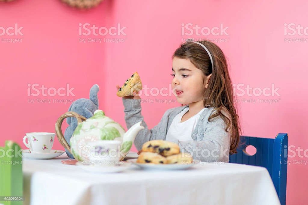 Cute girl eating a scone at her tea party table stock photo