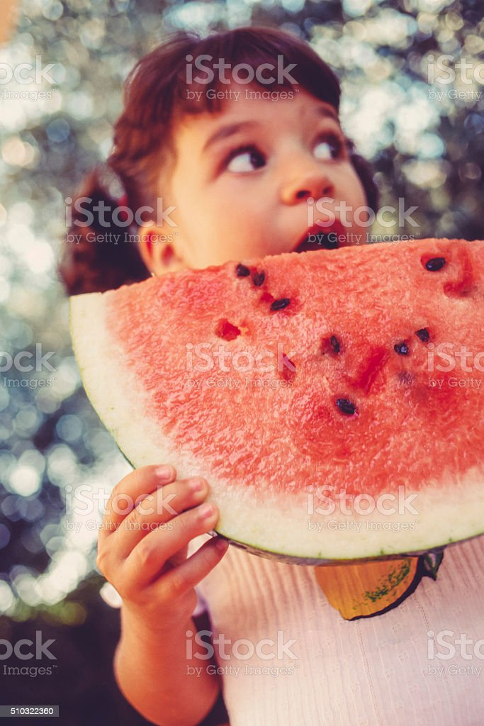 Cute girl eating a slice of watermelon stock photo