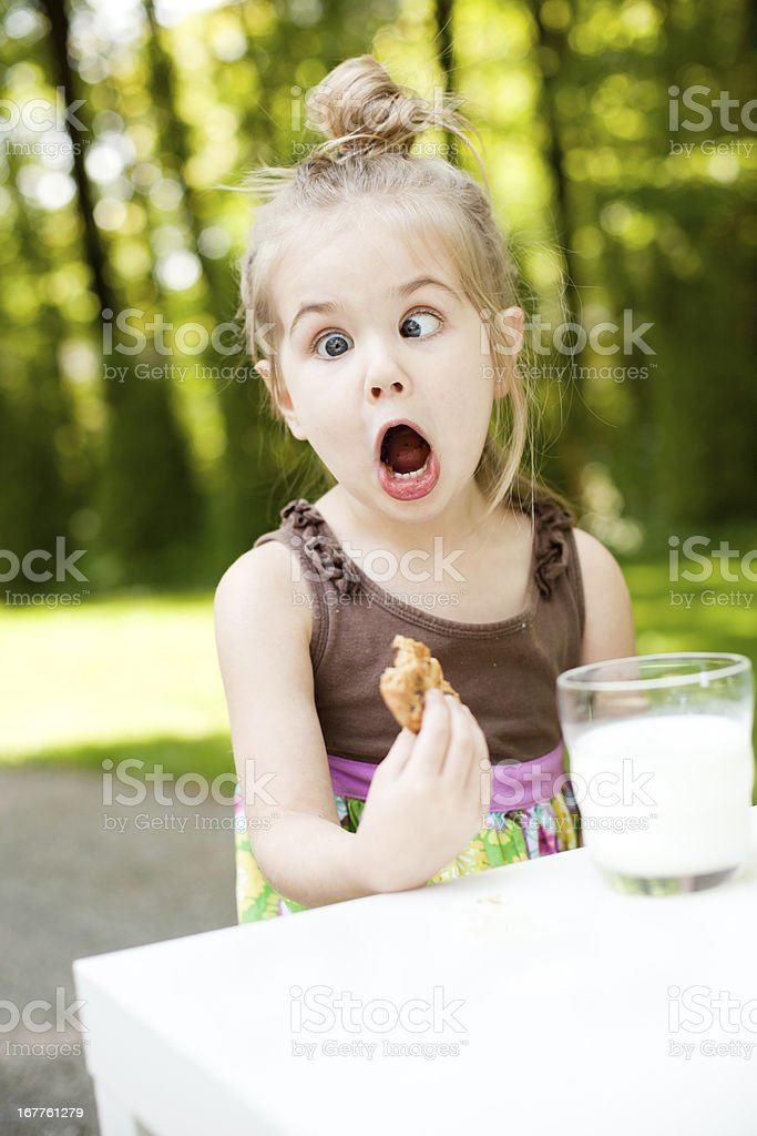 Cute Girl Eating Cookies and Milk Making a Face stock photo