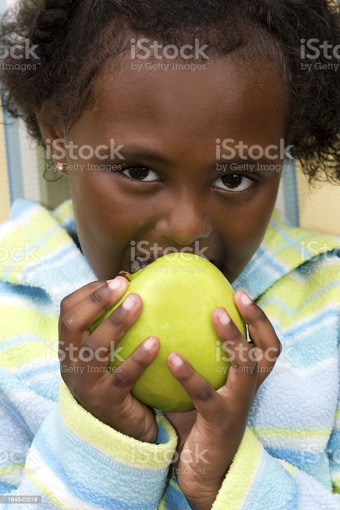 Cute girl eating green apple royalty-free stock photo