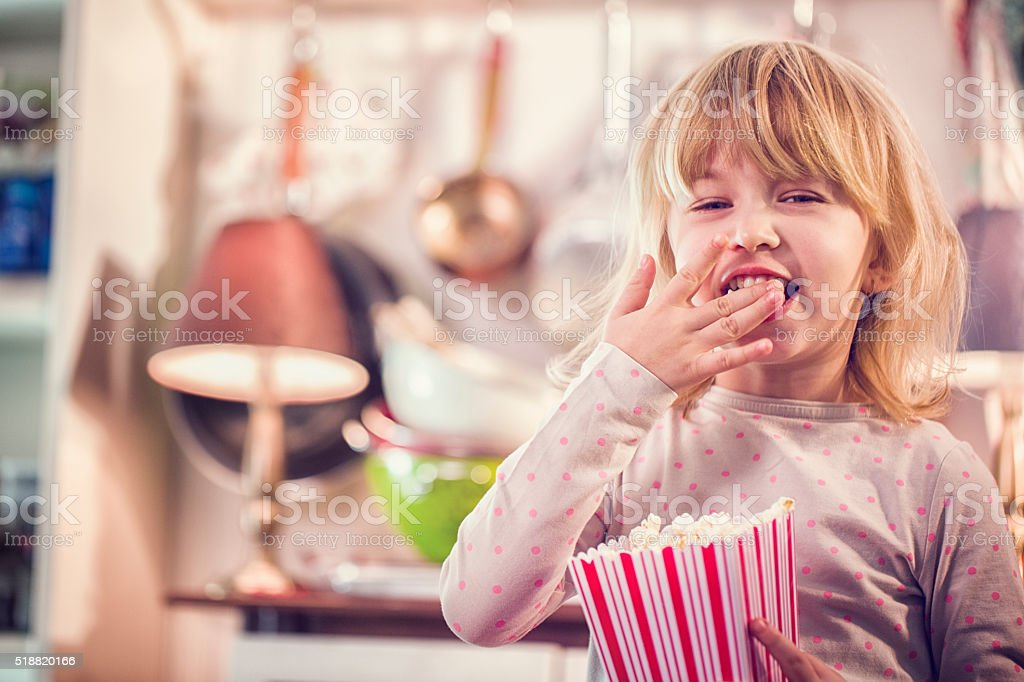 Cute Girl Eating Homemade Popcorn stock photo