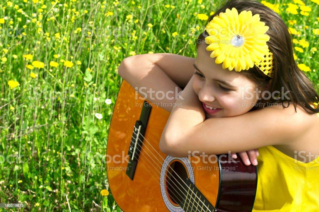 Cute girl enjoying with guitar to daisy field stock photo