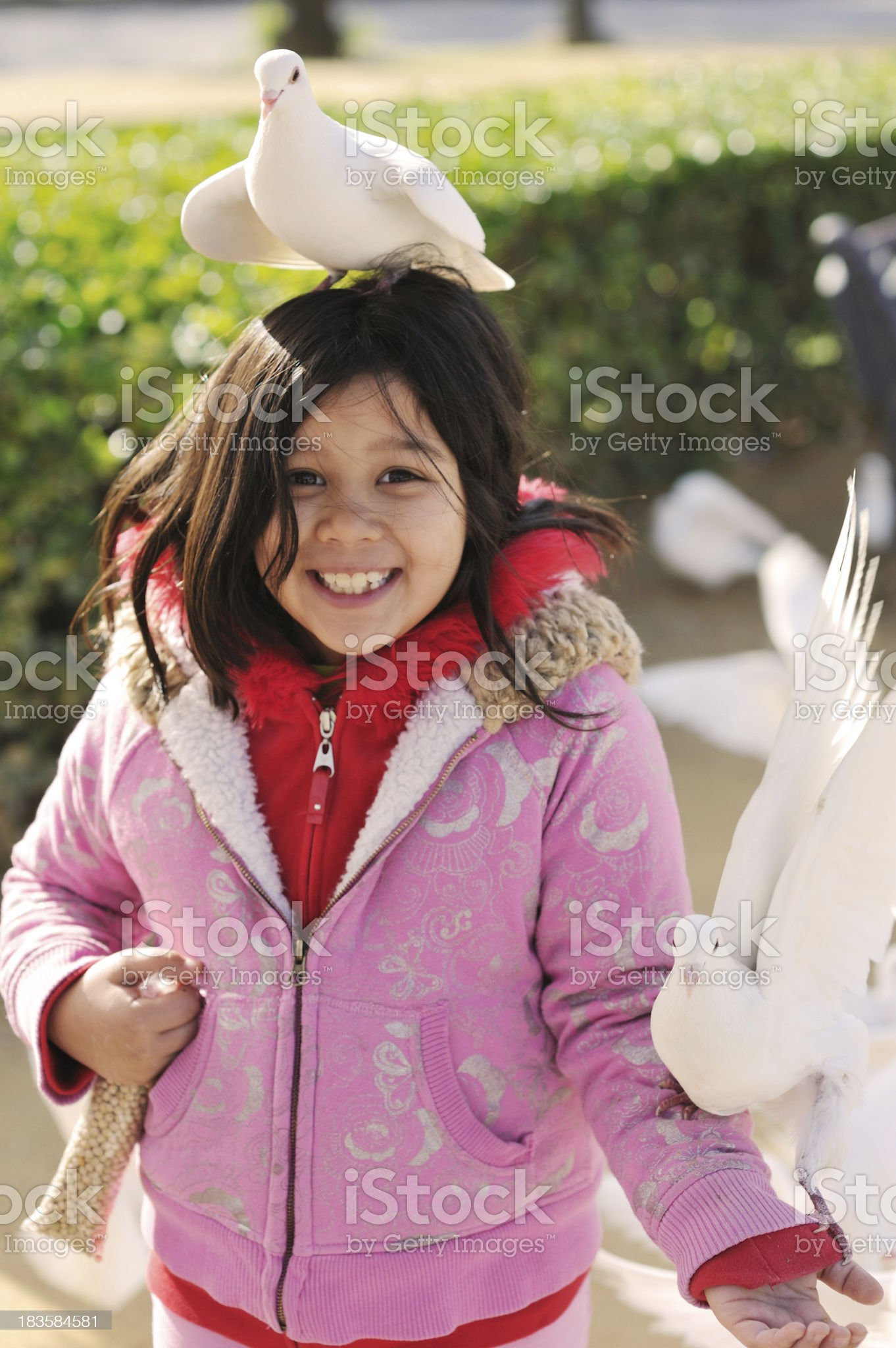 Cute girl feeding pigeons in Spain royalty-free stock photo