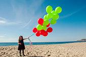 Cute girl having fun with ballons on her birthday