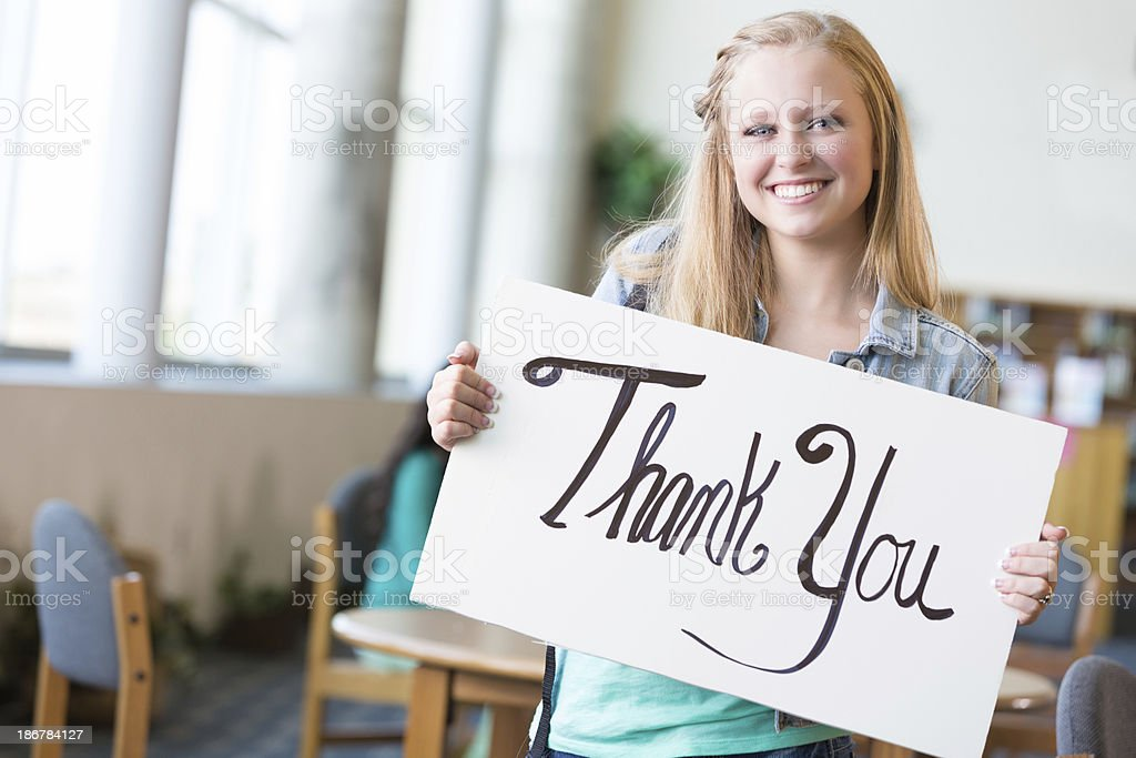 Cute girl holding a thank you sign in school library royalty-free stock photo