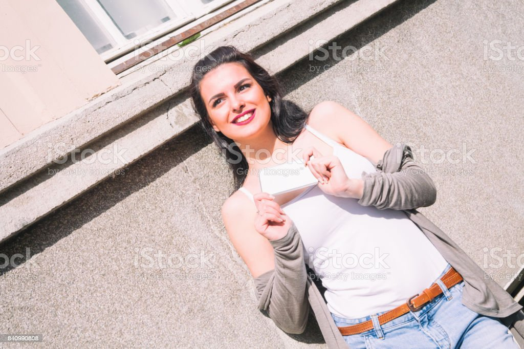 Cute girl holding cellphone on the street. stock photo