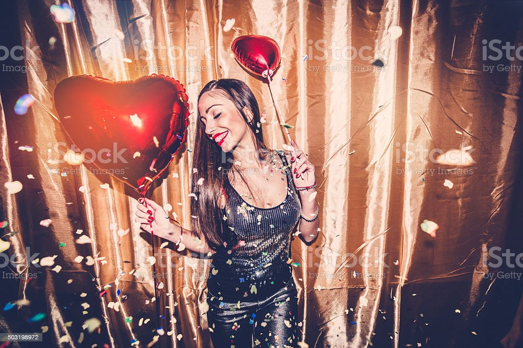 Cute girl holding red heart balloon stock photo