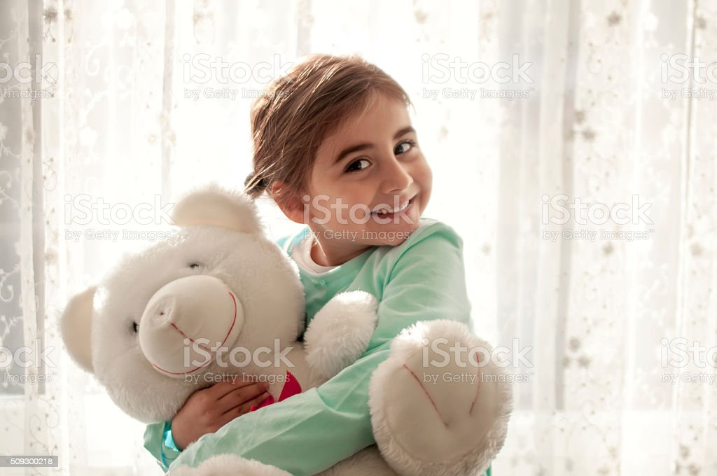 Cute girl hugging each other her teddy stock photo